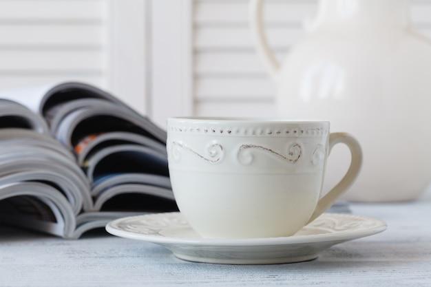 Стек журналов и белая чашка кофе на белом
