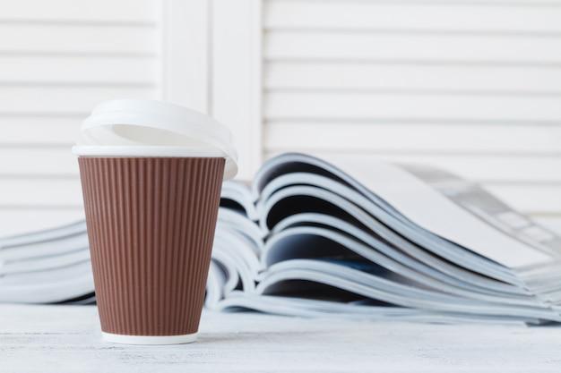 Журнал и кофе, чтобы пойти композиция крупным планом