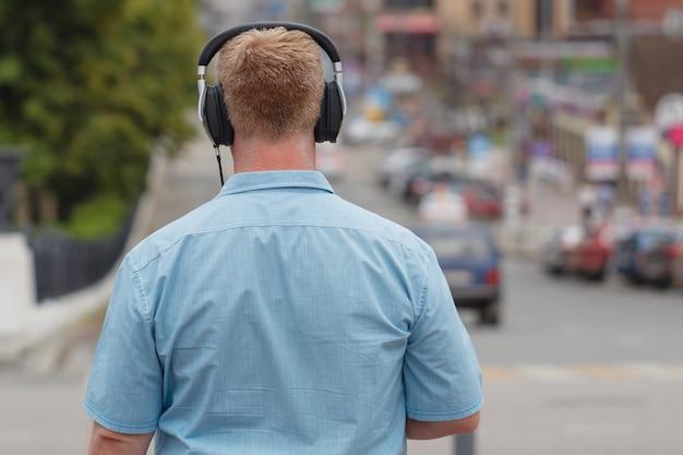 歩いて、スマートフォンでヘッドフォンで音楽を聴く男