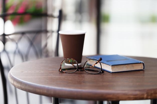 明るいテーブルの上のコーヒーの紙コップ