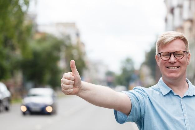 Человек стоит на улице города и приветствует такси