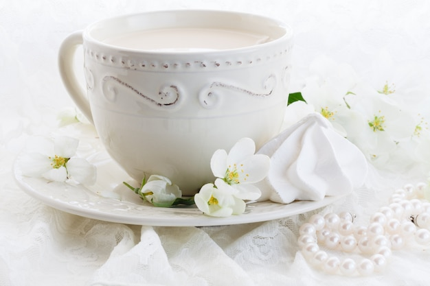 一杯のコーヒーと白い壁にピンクの桜