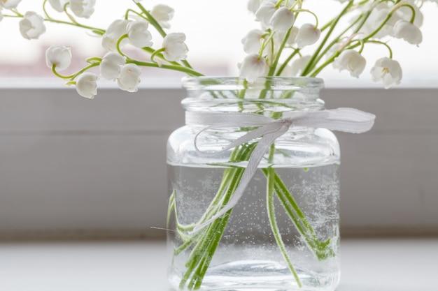 谷間のユリの花束は、木の表面にあるシンプルなガラスの花瓶に入っています。