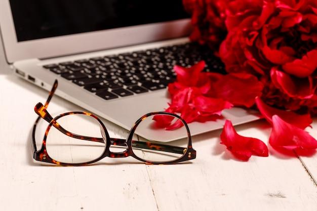 Букет из розовых пионов, ноутбук, смартфон, ручки, очки и блокнот на белом столе