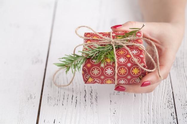 Женщина держит подарочную коробку в знак жеста