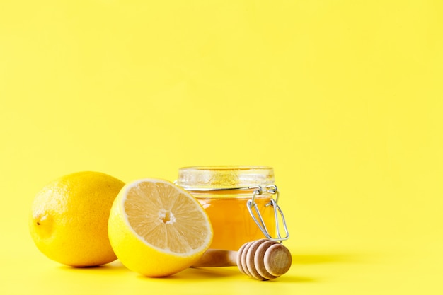 Баночка меда деревянной ложкой и лимонами