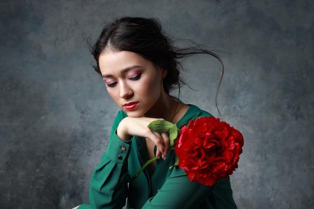 ピンクの牡丹の素敵な花束とエレガントなドレスで美しいセクシーなスタイリッシュな若い大人。スタジオ補正ショット