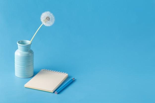 ノート、鉛筆、青い机の背景にタンポポ