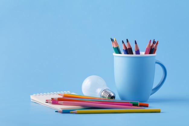 Куча цветных карандашей и лампочки на синей поверхности