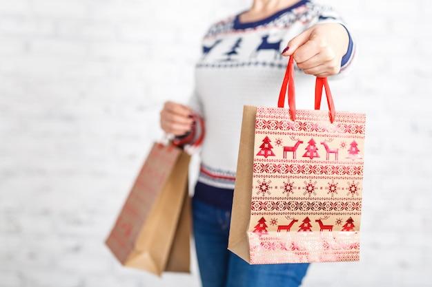 女性の手でクリスマスショッピングバッグ