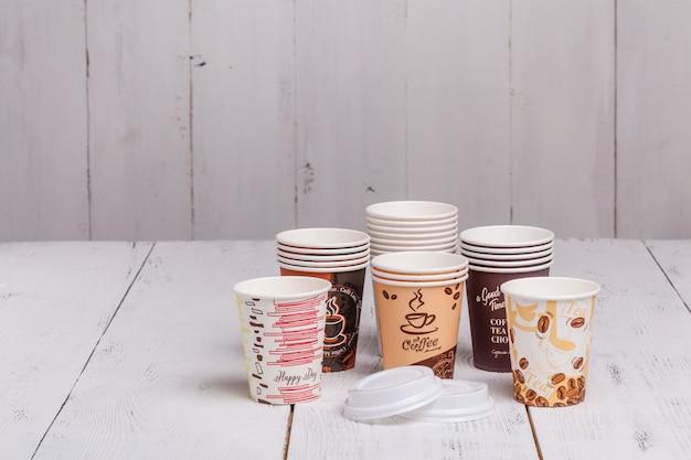 木製のテーブルに行くコーヒー用の使い捨て紙コップ