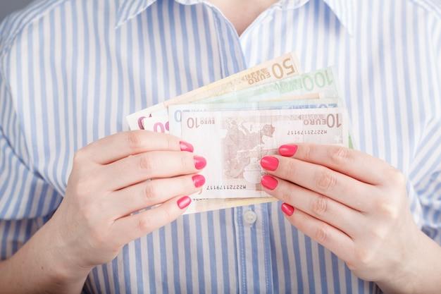 女性は手でお金を保持します