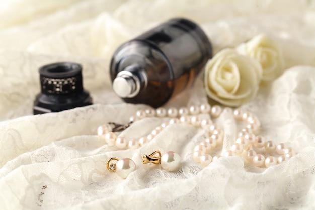 Женские духи в красивой бутылке, светлая стенка с аксессуарами для ухода и красоты