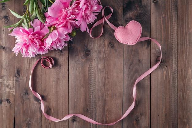 挨拶メッセージのコピースペースを持つ暗い素朴な木製の背景にピンクの牡丹の花。母の日と春の背景コンセプト