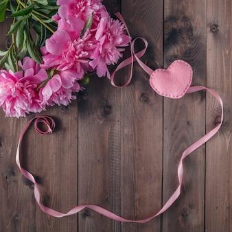 木製の背景に美しいピンクと白の牡丹