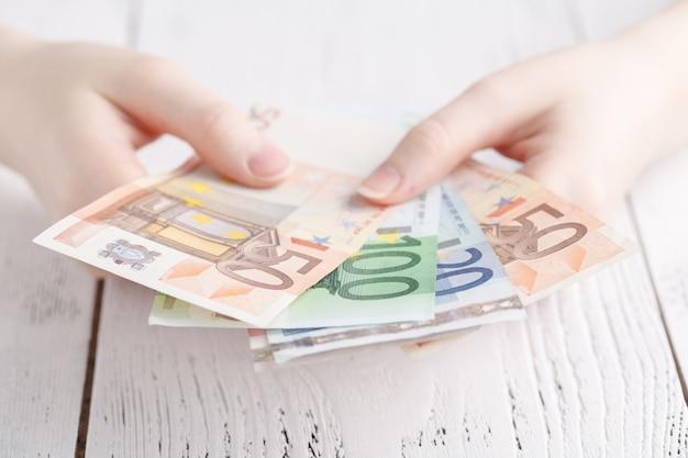 いくつかのユーロ紙幣を保持している女性の手のクローズアップ