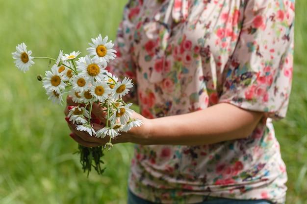 デイジーの花の花束を保持している女性