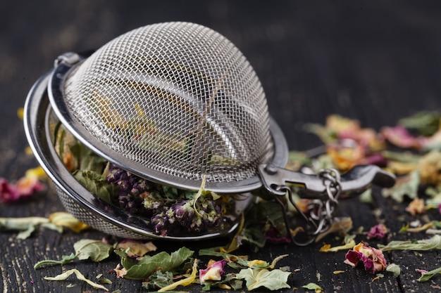 木製のテーブルにお茶の薬効があるハーブのヒープ
