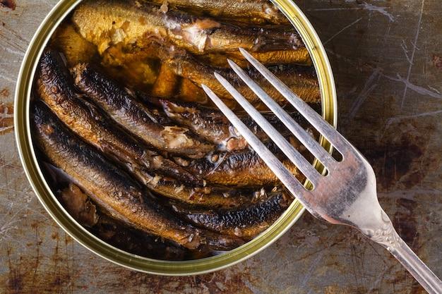 Открытые рыбные консервы и рыба на вилке