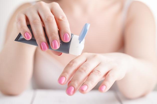 Женская рука в процессе нанесения крема