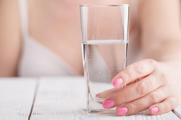女性の手でガラスに澄んだ水のしぶき