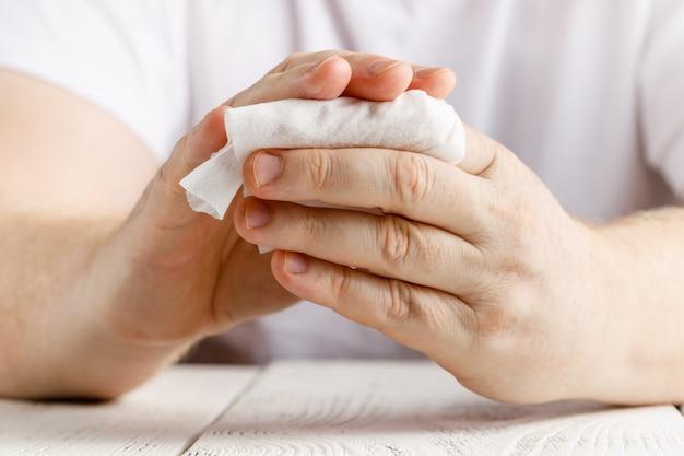 自宅やオフィスでの日、ウイルスや細菌からのナプキン消毒をホワイトアルコールティッシュクリーニングで拭く男の手の中央部のクローズアップ