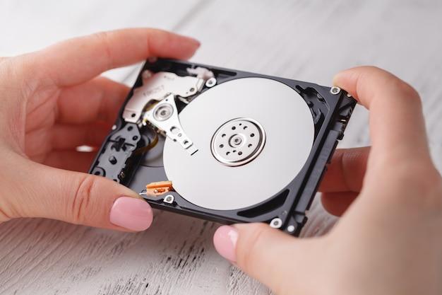 開いているハードディスクを保持している女性