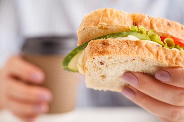 Перерыв на работе. голодный работник ест сыр сэндвич
