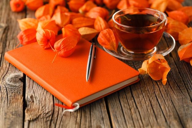 お茶、秋の静物、素朴な木製の上のカラフルな葉