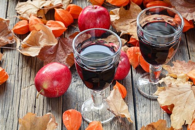 秋の葉のテーブルの上のグラスで赤ワイン
