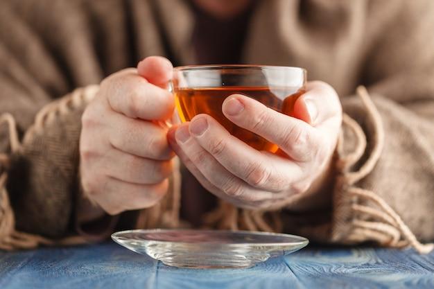熱いお茶を飲むセーターの男
