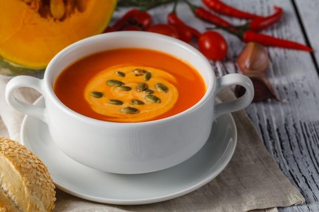 Жареный суп из тыквы и моркови с кремом и тыквенные семечки на белом фоне деревянные. копировать пространство