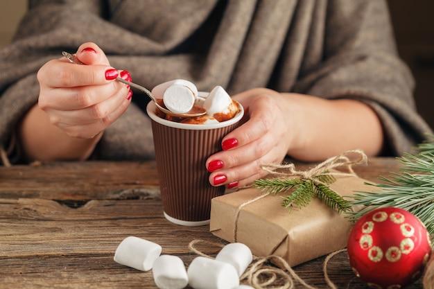 Женщина держит чашку горячего шоколада с зефиром