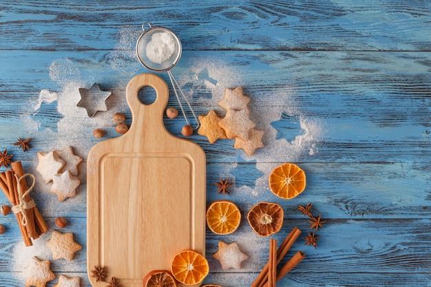 クリスマスの自家製ジンジャーブレッドクッキー、スパイス、テキストトップビューのコピースペースと濃い緑色の背景にまな板。休日、お祝い、料理のコンセプト。新年とクリスマスのポストカード