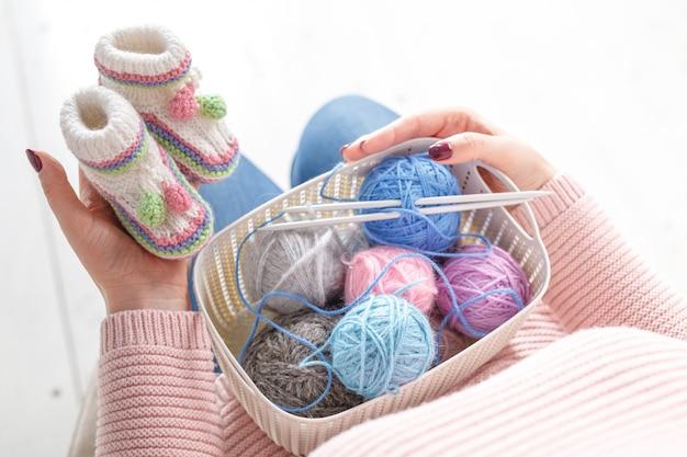 編み物のベビーシューズ、妊娠中の自家製の仕事の概念