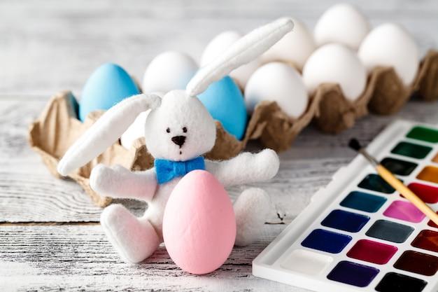 おもちゃのウサギとカラフルなイースターエッグ