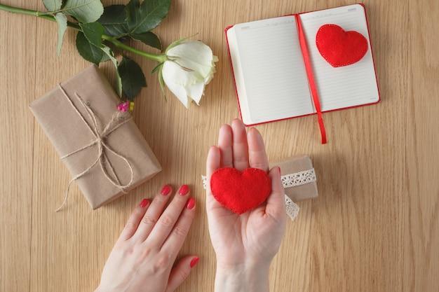 愛の概念。赤いハートを手で押し
