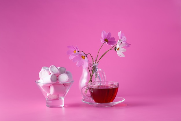 Розовый зефир на розовом фоне с цветами