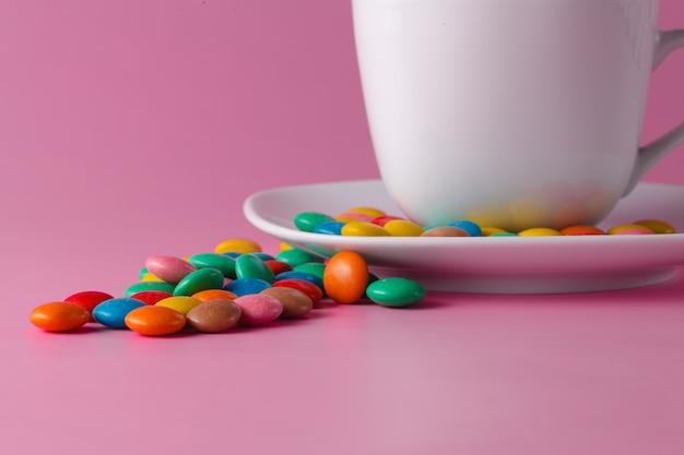Чайная чашка с цветными сладкими драже на блюдце