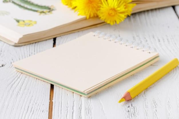 黄色のタンポポと白のノートのためのノート