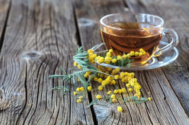 お茶のカップと素朴なテーブルの春の花