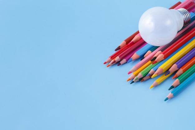 Куча цветных карандашей и лампочки на синем фоне