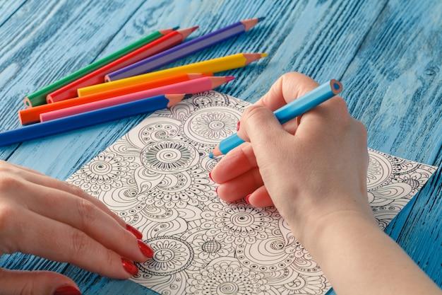 大人の塗り絵の色鉛筆の抗ストレス傾向。ストレス解消画家を描く趣味女性の手