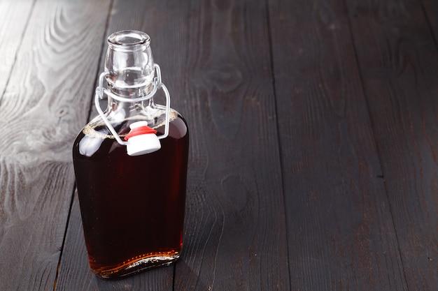 Алкогольный напиток домашнего приготовления в бутылке на столе