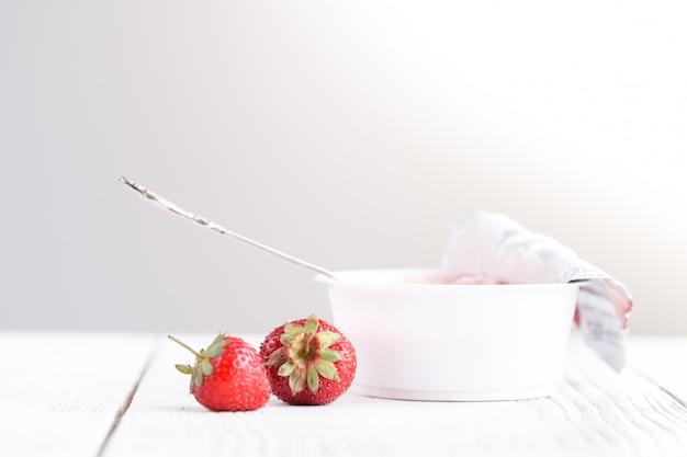 女性の手でスプーンで白いテーブルにミルククリームとイチゴ