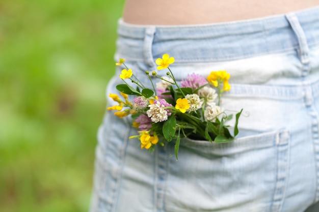 Цветок в большом кармане джинсовых брюк, летний концепт