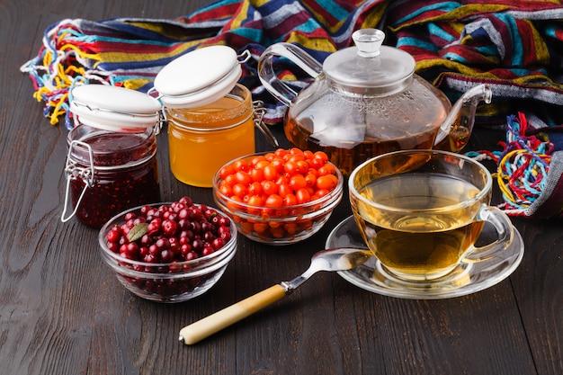 健康的なコンセプト。木製のテーブルの上のガラスのコップにクランベリー、蜂蜜、タイムと冬のベリーティー伝統的な医学の代替