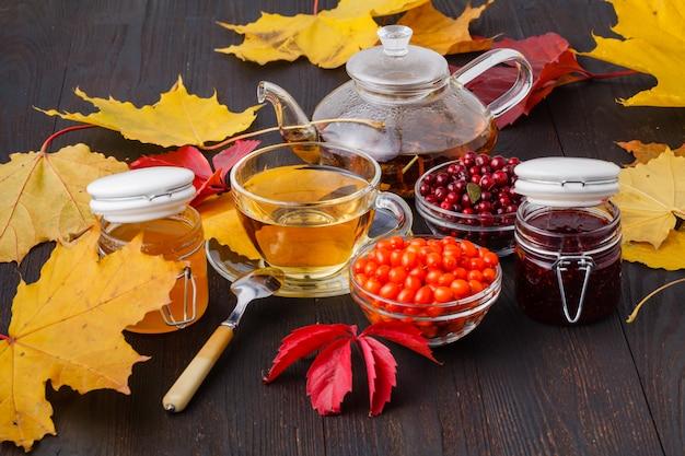 秋の環境の木製テーブルに蜂蜜と海クロウメモドキの果実のお茶
