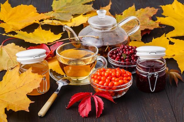 健康的な背景。野生のベリーとラズベリーのジャム、蜂蜜、紅茶秋の木製テーブル