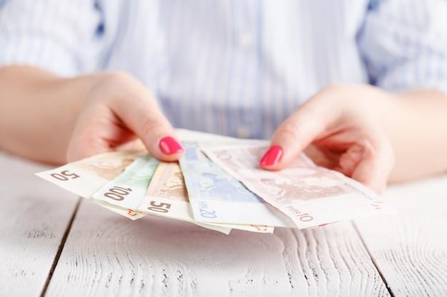 Женские руки с банкнотами дают деньги